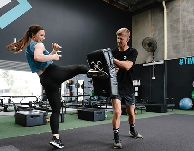 Woman and exercise trainer doing leg kicking workout
